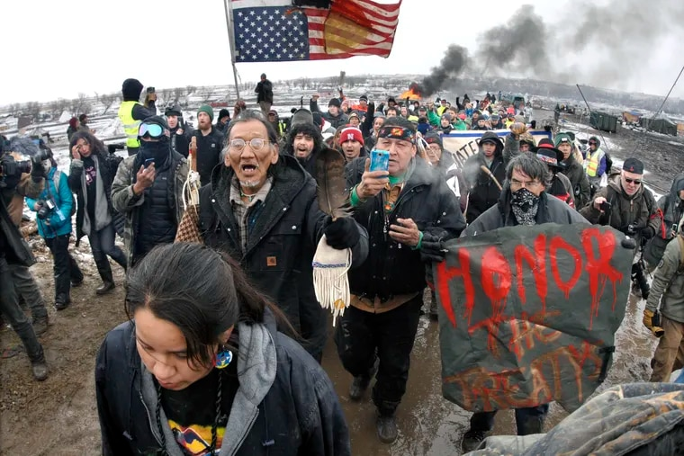 In this Feb. 22, 2017, file photo, a large crowd representing a majority of the remaining Dakota Access Pipeline protesters march out of the Oceti Sakowin camp before the deadline set for evacuation of the camp mandated by the U.S. Army Corps of Engineers near Cannon Ball, N.D.