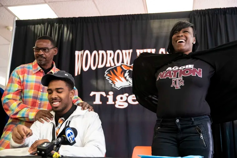 Woodrow Wilson defensive end Fadil Diggs signs with Texas A&M in front of his father, Mark Diggs (left), while his mother, Toma Robinson, shows off her Aggie Nation t-shirt.