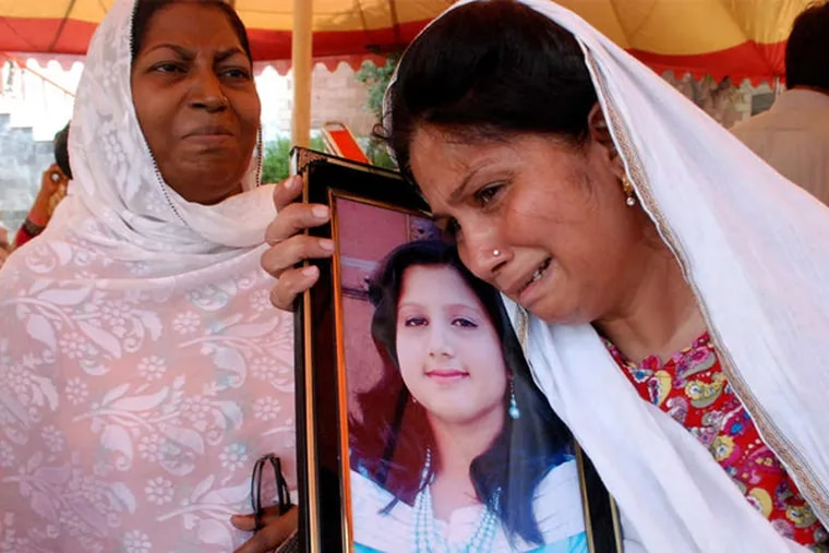 A Pakistani Christian on Tuesday holds a picture of her daughter, who was killed in a suicide bombing Sunday outside a church.