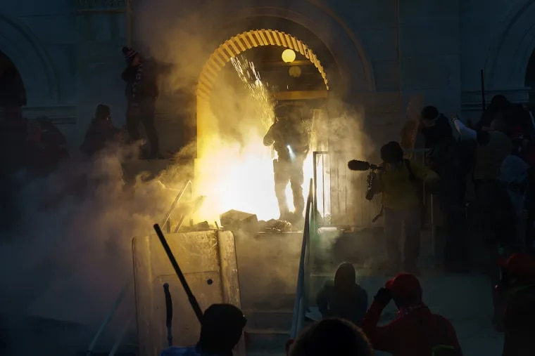 Police clear a doorway that was previously under attack with what appears to be a flash grenade and tear gas at the capital building on Wednesday in Washington, DC. The United States Capitol Building was breached by thousands of Pro Trump supporters.