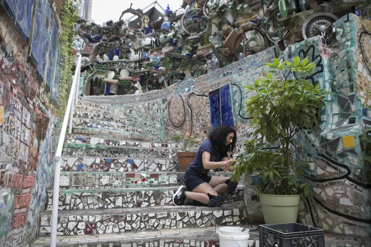 Yaara Ben-Dor removes and restores part of the tiling on the steps of Philadelphia's Magic Gardens on South Street on the morning of Tuesday, July 31, 2018.