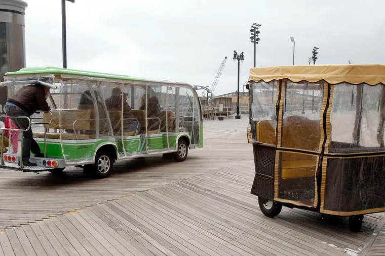 One of the prototype jitneys drives past a more familiar rolling chair on the Boardwalk.