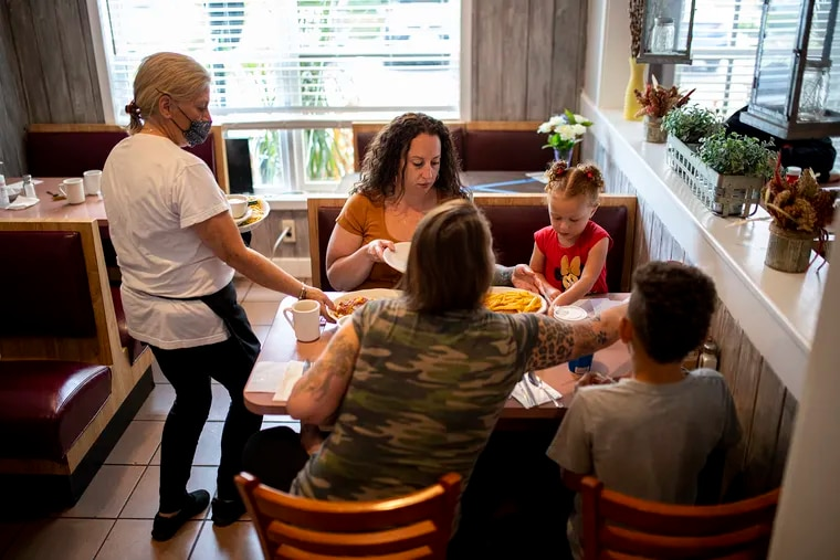 Clockwise from left, Lakeside Diner owner Debbie Brindisi brings food for Cherish Moscagiuri, her two kids Elliana Moore and Travis Moore, and Lauren Brousell, in Lacey Township, N.J., on Tuesday.