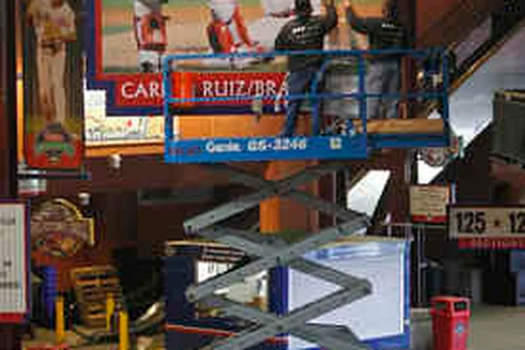 Luis Rivera (left) and Dave Knowles install a giant photo at Citizens Bank Park of catcher Carlos Ruiz and reliever Brad Lidge celebrating the Phillies' 2008 World Series victory.