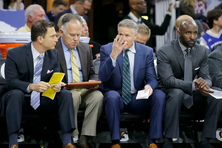 Sixers Head Coach Brett Brown (with hand up) sits on the bench with assistant coaches Billy Lange (left), Jim O'Brien (second left) and Lloyd Pierce (right) against the Toronto Raptors on Wednesday, January 18, 2017 in Philadelphia. Pierce interviewed for the Atlanta Hawks' coaching job on Friday.