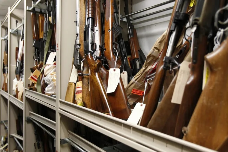 A report by analysts with Raymond James says the number of applications for gun-purchase background checks is up. These guns were inside the Firearms Inspection Unit in Philadelphia in August 2012. ( DAVID MAIALETTI / Staff