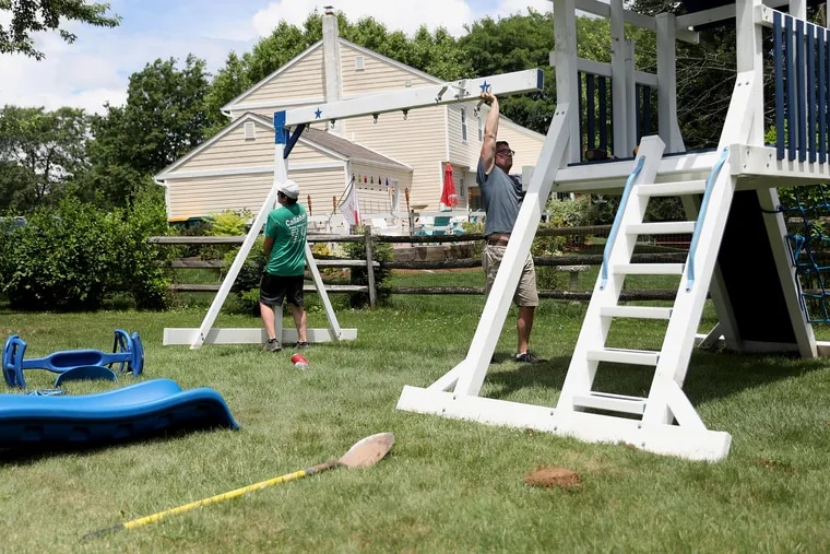 Elite Outdoor Structures co-owner Steve Moffitt (right) and installer Billy Feeley assemble a playset behind a customer's home in Lansdale on July 1. The coronavirus pandemic has increased demand for outdoor playsets, which are selling out quickly.