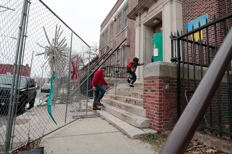 Parents and children navigate temporary fences and support beams that are holding up the second floor of Vare Recreation Center in South Philadelphia. The facility is set to get a $14 million renovation as part of the city's Rebuild program.