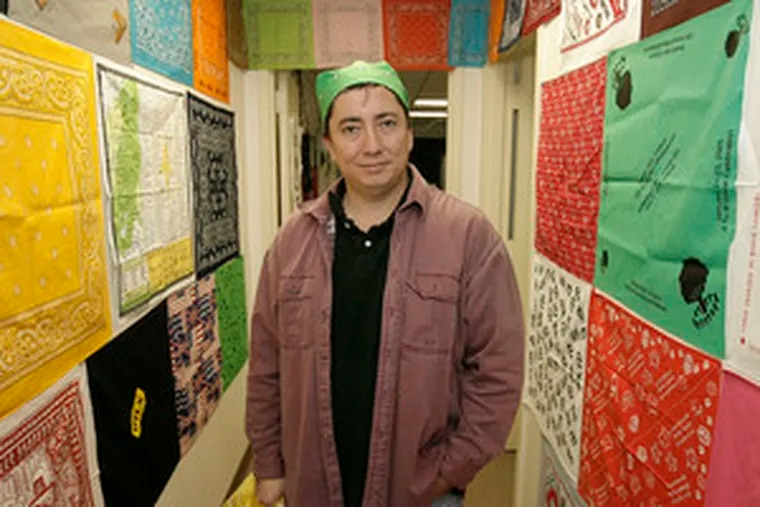 Daniel Weaver, at his warehouse in Hainesport, is flanked by samples of the bandanas that are a big part of his business.