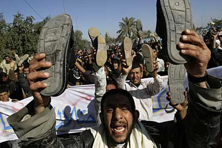 Iraqis raise their shoes as hundreds demanded a release for Iraqi journalist Muntadhar al-Zeidi who threw his shoes at US President George W. Bush in Kufa, Iraq, Friday. Dec. 19, 2008.  (AP)