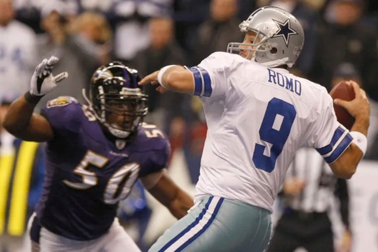 Cowboys quarterback Tony Romo gets set to throw as Ravens defender Antwan Barnes charges in. Romo threw for two TDs but was intercepted twice.