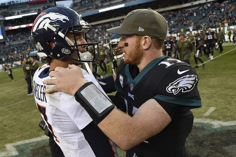 Eagles quarterback Carson Wentz meets Broncos quarterback Brock Osweiler after the game the Eagles won, 51-23, at Lincoln Financial Field.