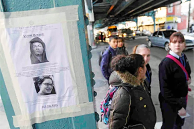 Under the El in Kensington, pedestrians crossing Kensington Avenue pass a Citizens' Crime Commission reward poster for a man wanted for questioning in last month's strangulation of Elaine Goldberg. (Clem Murray / Staff Photographer)