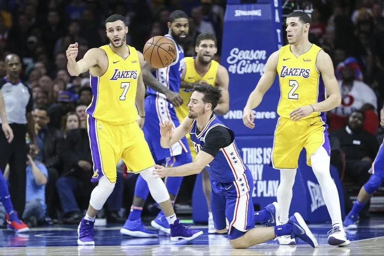 The Sixers' T.J. McConnell throws a pass from his knees between Lakers Larry Nance Jr. (7) and Lonzo Ball (2) during the third quarter.