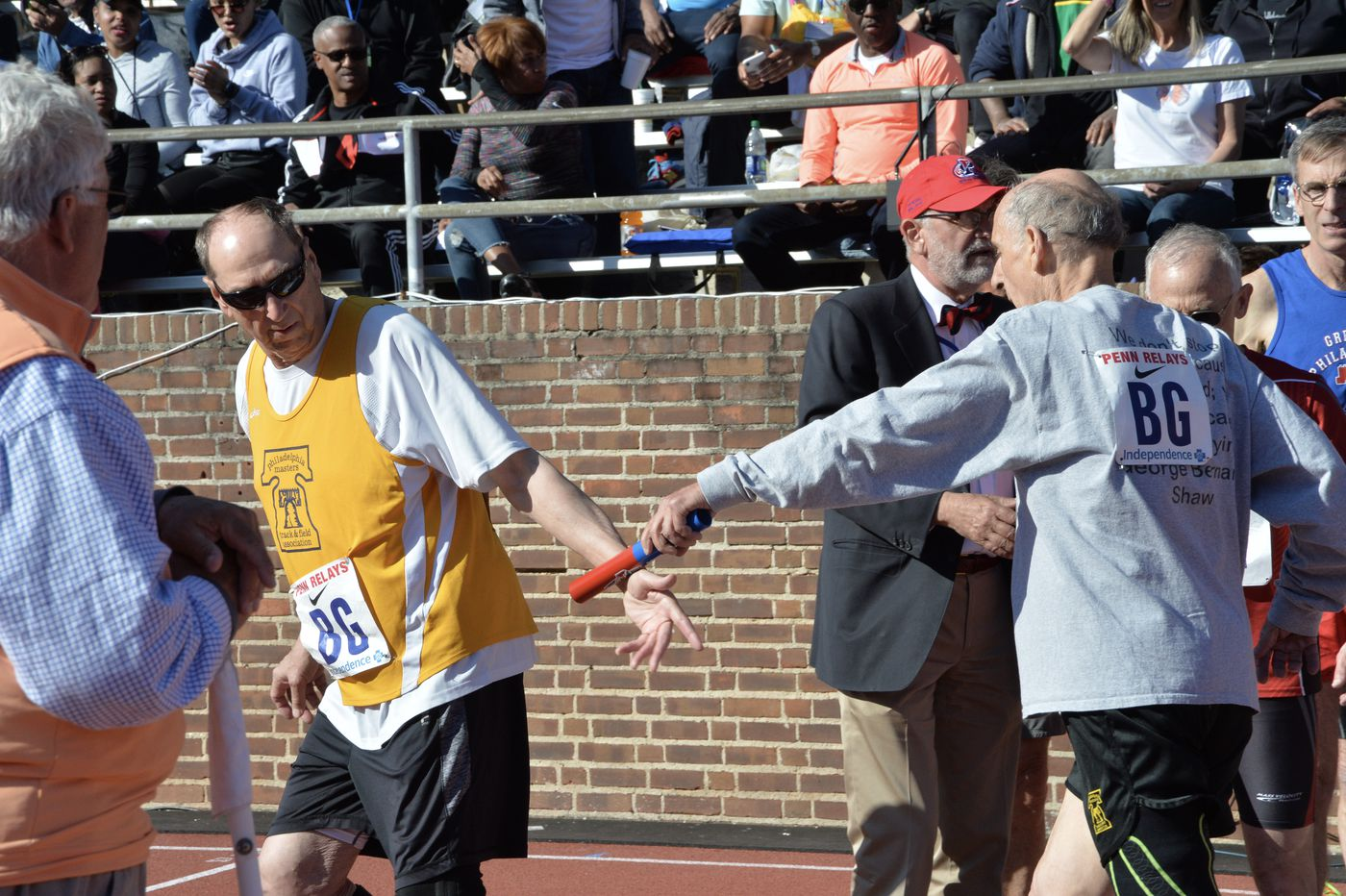 Dave Marovich, left, takes baton exchange from Bruce Rubin, right, after the leadoff leg of the 4x400-meter relay at the 2019 Penn Relays.