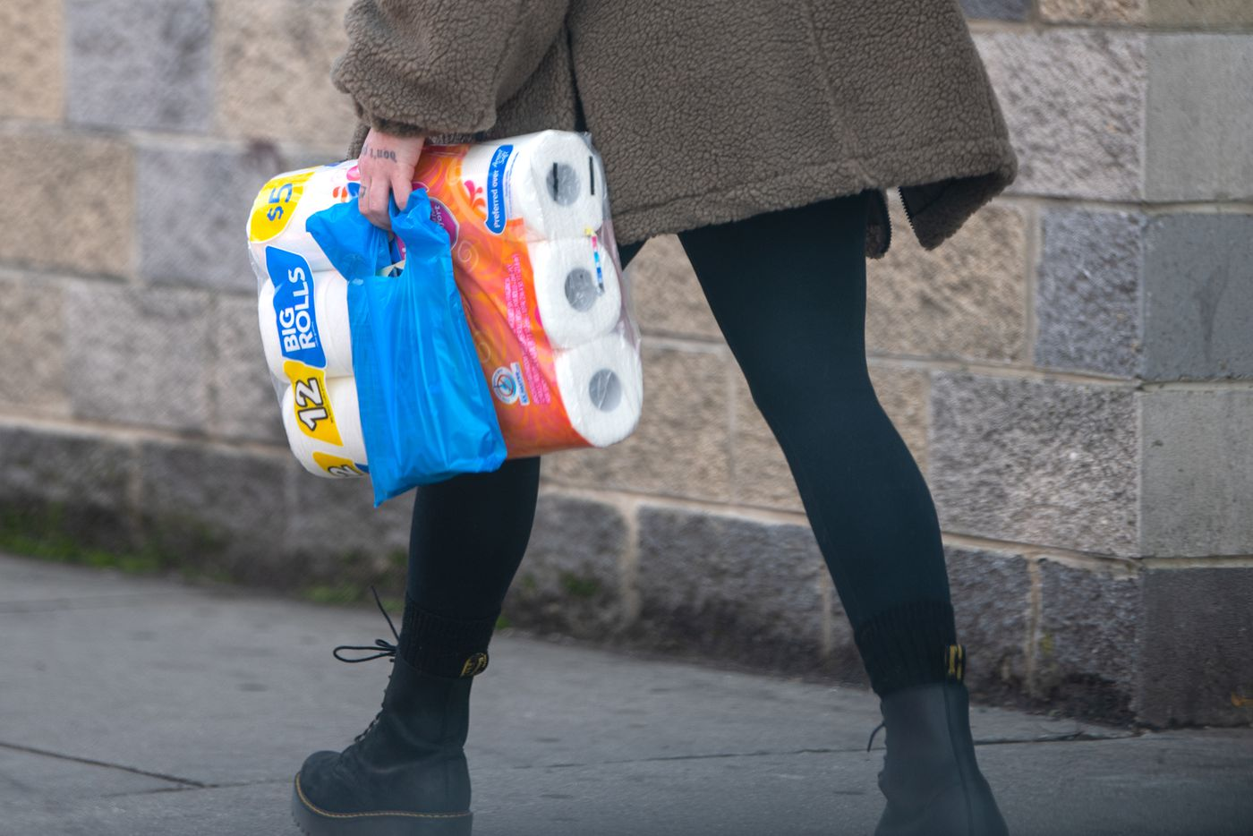 An unidentified woman walks carrying toilet paper rolls in Philadelphia, Pa. Tuesday, March 17, 2020. The household staple has consistently been out of stock during the coronavirus outbreak.