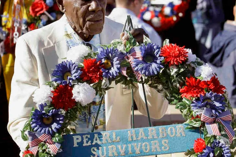 Survivor Nelson Mitchell, 90, of Phoenix, walks with a wreath to the Arizona Anchor Memorial on Tuesday. More at the memorial website via http://go.philly.com/pearl.