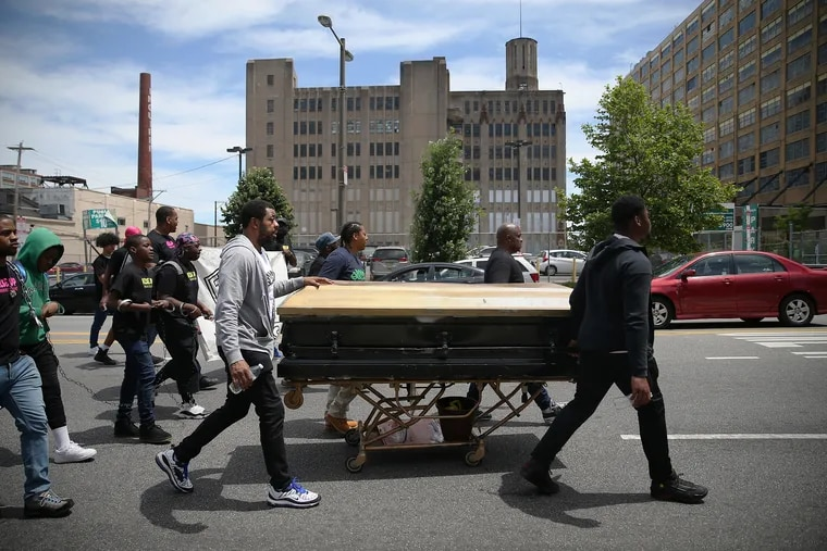 """Activists (from left) Darryl Booker, Fatimah Martin, Terry Starks, and Yaddi Jones wheel a casket down North Broad Street toward City Hall in Philadelphia as they march against gun violence and other issues on Tuesday, May 21, 2019. The """"Rise Up Break the Chains Youth March,"""" organized by 13-year-old Ryshee Shaw, went down Broad Street from York Street to City Hall on election day to bring attention to bullying, gun violence, mass incarceration, mental health, substance abuse, racial profiling and youth homelessness."""