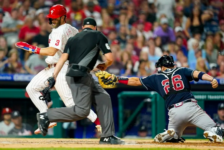 The Phillies' Bryce Harper steals home after getting past the tag of Braves catcher Stephen Vogt in the fifth inning Friday night.