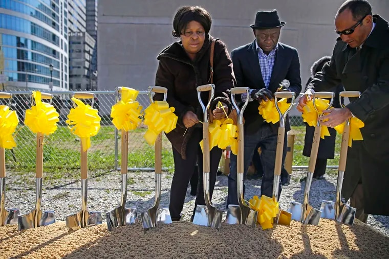 Kadie Conteh (left), Aiah Boya (center) tied yellow ribbons on the shovels used for a memorial at the Salvation Army site for victims of the building collapse. The trial is on hiatus until Nov. 15.