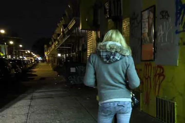 A young woman named Anna walks a street near Kensington Avenue on Monday night. (Steven M. Falk / Staff Photographer)