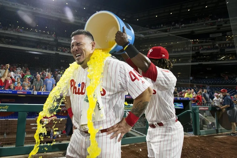 Wilson Ramos, gets a cooler dumped on him by fellow Venezuelan Odubel Herrera after his first game as a Phillie.