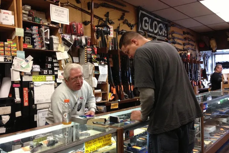 Fred Delia, owner of Delia's Gun Shop in the Wissinoming section, helps a customer on Wednesday, Dec. 19. Delia says his store has been busier than usual since the Newtown school massacre due to concerns that new gun control measures will make it harder to buy firearms. (Emily Babay / Staff)