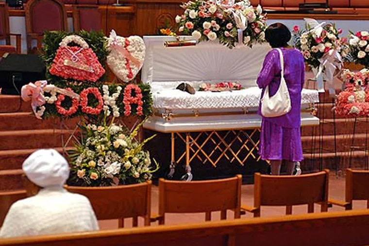"""A large floral arrangment was placed next to Aaliyah Griffin's coffin spelling out her nickname, """"Pooka."""" (Tom Gralish/Staff Photographer)"""