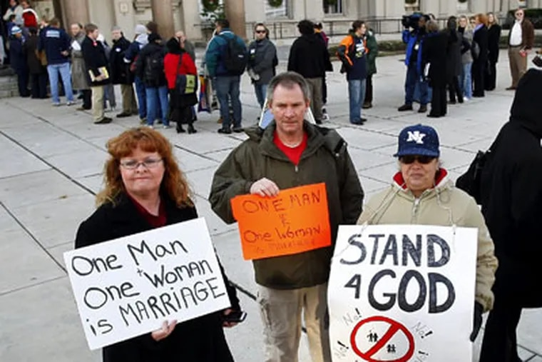 People carry signs as they walk in front of the New Jersey Statehouse where lawmakers held a debate over whether to legalize gay marriage in Trenton, N.J. (AP Photo / Mel Evans)