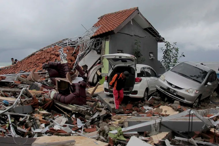 A man inspects the damage suffered by a building following a tsunami in Anyar, Indonesia, Sunday, Dec. 23, 2018. An eruption of one of the world's most infamous volcanic islands is believed to have triggered a tsunami that killed hundreds of people in Indonesia during a busy holiday weekend. The waves smashed onto beaches at night without warning, ripping houses and hotels from their foundations in seconds and sweeping terrified concertgoers into the sea. (AP Photo)