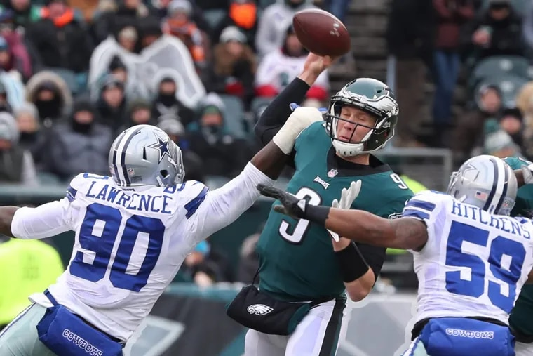 Eagles quarterback Nick Foles is hit while he is throwing the ball by Dallas' Demarcus Lawrence (90) and pressured by Anthony Hitchens (59) in the first quarter of Sunday's game.