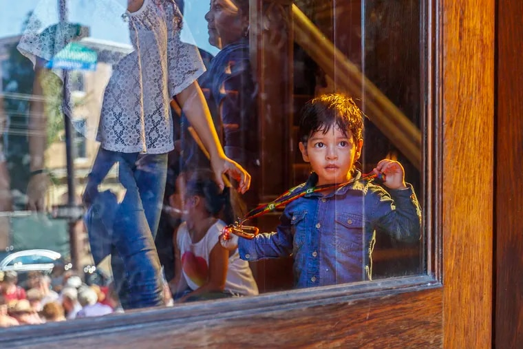 Yamie Reyes, 7, looks out the front door from the inside of the First United Methodist Church of Germantown, seeing the crowd that gathered outside to welcome him, his family and the Thompson family from Jamaica.
