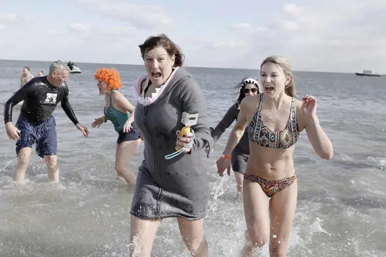 File Photo: Participants react after taking part in Sea Isle City's polar bear plunge in February 2013. The deep freeze gripping the region is prompting organizers to cancel New Year's Day plunges   at the Shore.