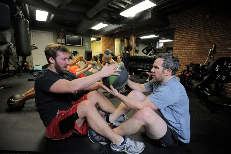 Left to right, Woody Heffern, marketing, and Jared Kelly, director of marketing, Agora Inc. pass a medicine ball while doing sit ups. Committing to new year's resolutions like going to the gym means keeping expectations realistic so as not to lead to disappointment.