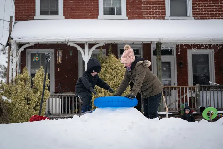 Armani Hennessey, 5, receives help from his cousin Amanda Guzik, 17,  preparing to sled down a hill in the front yard in Norristown on Wednesday.
