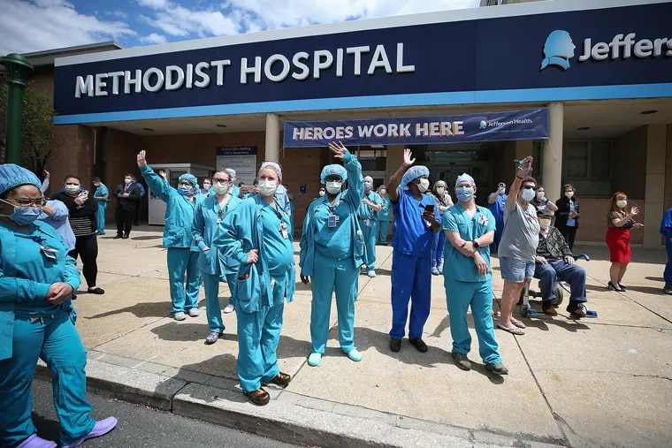 Medical staff gathered outside Jefferson Methodist Hospital in Philadelphia wave to a vehicle honking in support on Monday.