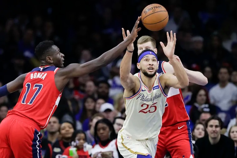 Sixers guard Ben Simmons goes after the loose basketball against Washington Wizards guard Isaac Bonga (left) and  forward Davis Bertans during the third quarter on Saturday night's game at the Wells Fargo Center.