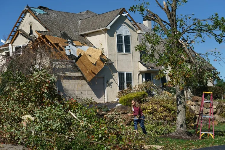 Cindy Bevilacqua moves branches in her daughter's yard, after an EF-2 tornado ripped through Chelsea Court in Thornbury Township.