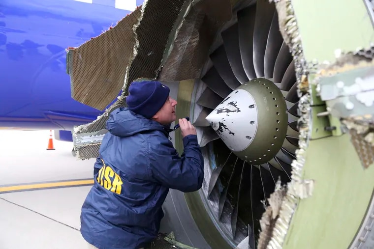 In this Tuesday, April 17, 2018 photo, a National Transportation Safety Board investigator examines damage to the engine of the Southwest Airlines plane that made an emergency landing at Philadelphia International Airport in Philadelphia. A preliminary examination of the blown jet engine of the Southwest Airlines plane that set off a terrifying chain of events and left a businesswoman hanging half outside a shattered window showed evidence of metal fatigue, according to the National Transportation Safety Board.