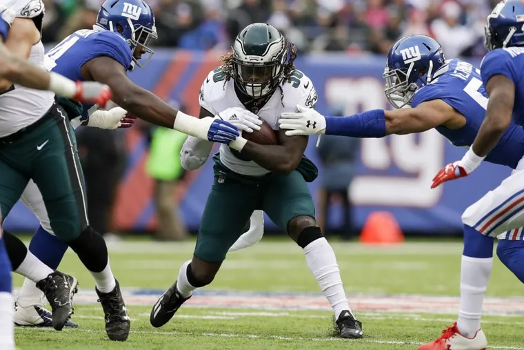 Jay Ajayi tries to get past Giants defensive end Olivier Vernon (left) and defensive tackle Dalvin Tomlinson (right).