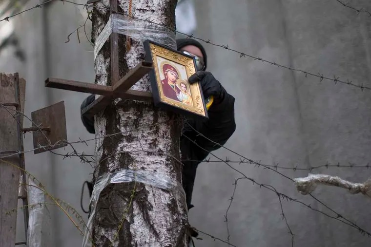 A Pro-Russian activist sets an Orthodox icon atop a barricade in Slovyansk, Ukraine. The activists vow to dig in despite diplomatic pressure and an agreement that they depart.