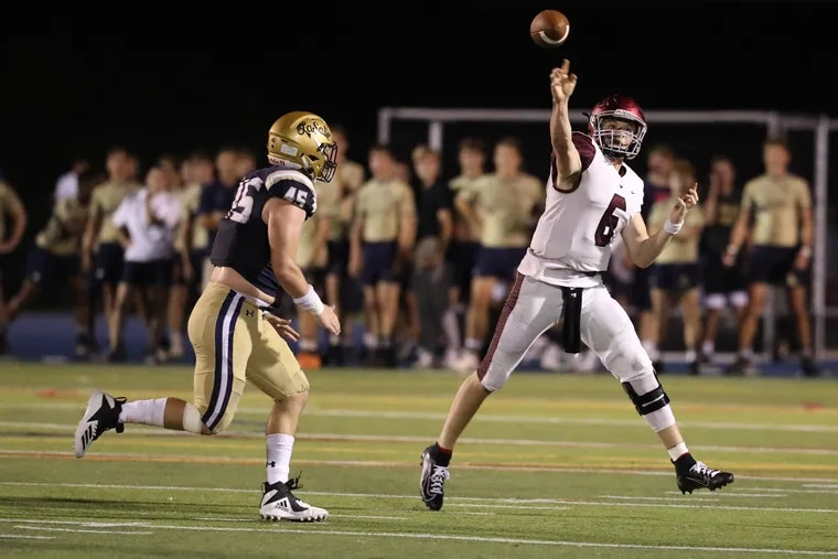 Kyle McCord of St. Joseph's Prep rolls out to pass under pressure from Timothy Barrett of La Salle during the Philadelphia Catholic League football clash between the two old rivals on Sept. 28, 2019.