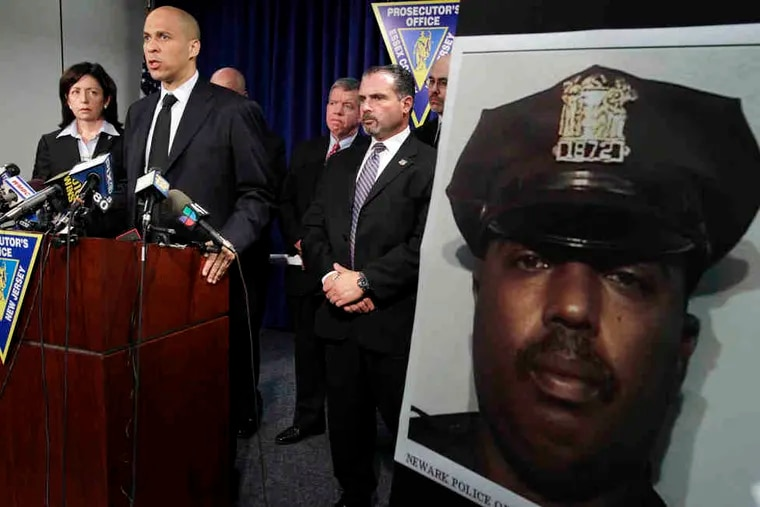 Officer William Johnson's photo is shown at a news conference about his killing. Among those answering questions were (from left) Carolyn Murray, acting Essex County prosecutor; Mayor Cory Booker; and Samuel DeMaio, acting police director.