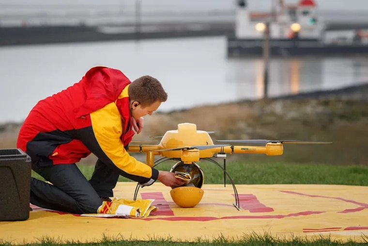 An employee places a parcel into the cargo storage pod of a DHL delivery drone during testing by Deutsche Post's parcel delivery unit in Norddeich, Germany. Deutsche Post and DHL handled more than one billion items in Germany last year, a market share exceeding 42 percent of parcel deliveries by value. The trial run may help Deutsche Post stake a claim to a part of the logistics chain in which postal operators and express service providers are increasingly being challenged by Internet retailers.