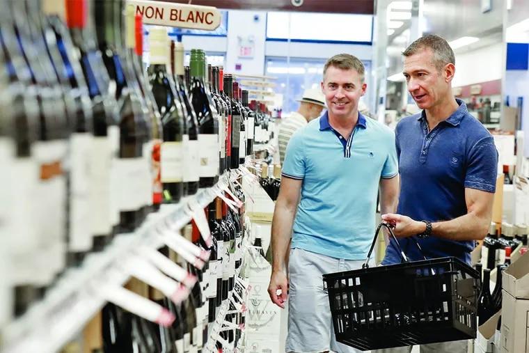 Stephen Betts (left) and husband Michael Sweeney shop at Fine Wine & Good Spirits, in Philadelphia's Gayborhood.