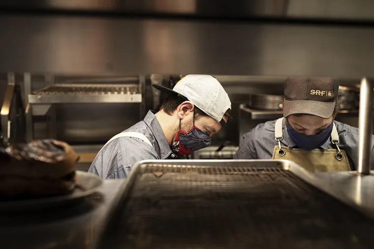 Chefs Scott Calhoun (left) and David Feola working in the kitchen at Ember & Ash, 1520 E. Passyunk Ave.