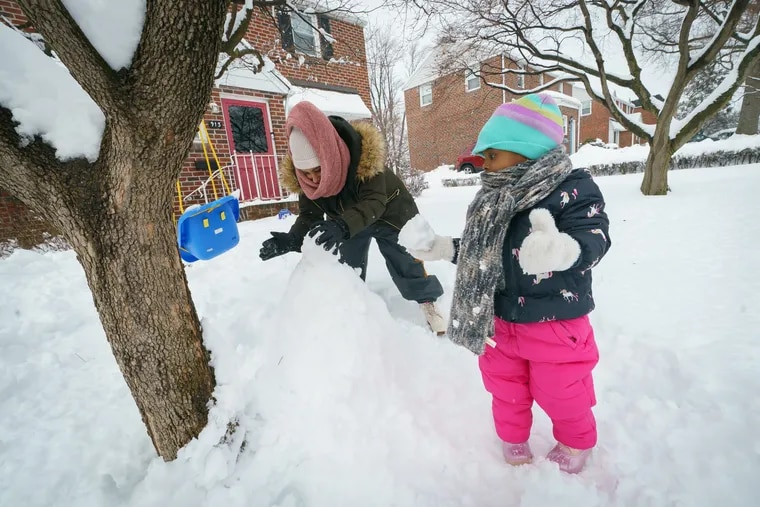 Latinya Jones and her daughter Lailah build a snowman in Norristown on Tuesday.