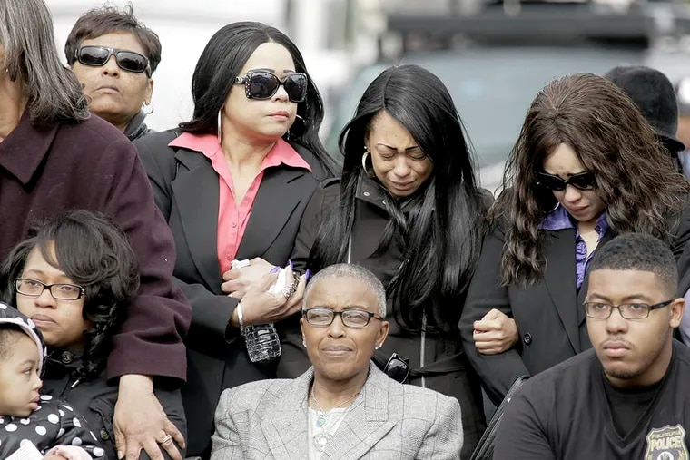 Family members of slain Philadelphia Police Officer Robert Wilson III watch as the police procession marches to his viewing at Francis Funeral Home in West Philadelphia on March 13, 2015. ( ELIZABETH ROBERTSON / Staff Photographer )
