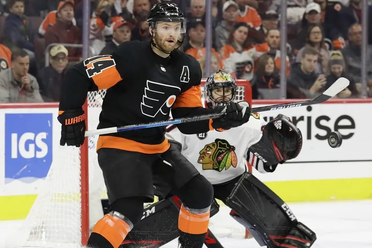 Flyers center Sean Couturier watches the puck during the first-period Saturday against Chicago goaltender Corey Crawford. Couturier had two goals in the Flyers' 4-0 win.