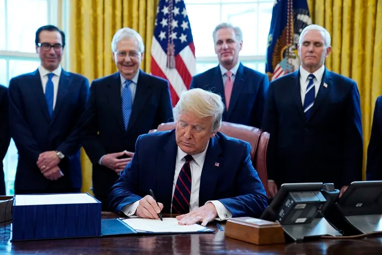President Donald Trump signs the coronavirus stimulus relief package, at the White House, Friday, March 27, 2020, in Washington, as from left, Treasury Secretary Steven Mnuchin, Senate Majority Leader Mitch McConnell of Ky., House Minority Kevin McCarthy of Calif., and Vice President Mike Pence, look on.